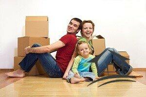 семья с коробками на полу новой квартиры